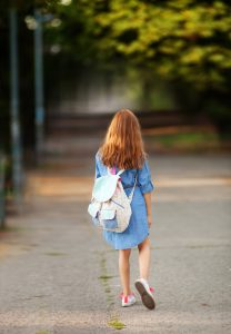 Seeking professional help for your child | photo of rear view of sad lonely girl walking with backpack