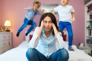 ADHD Kids | photo of kids jumping on bed behind frustrated mom