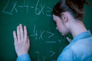 Dyscalculia Facts | Photo of teenage girl at chalkboard leaning head against board displaying math problem