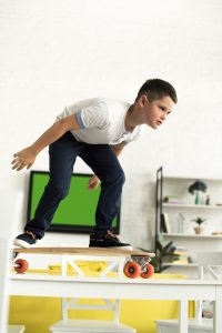 ADHD Facts | photo of child riding skateboard on kitchen table