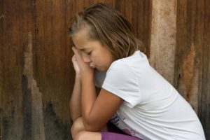 Helping your anxious child | photo of sad young girl leaning against door