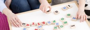 Dyslexia Facts | photo of hands of adult and child arranging block letters on magnet board