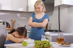 ADHD Diet For Kids | photo of frustrated mom glaring at child who won't eat at breakfast table