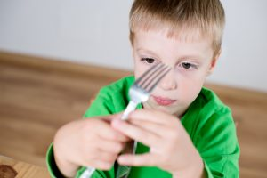 ADHD Diet For Kids | Photo of young boy staring at fork while waiting at table