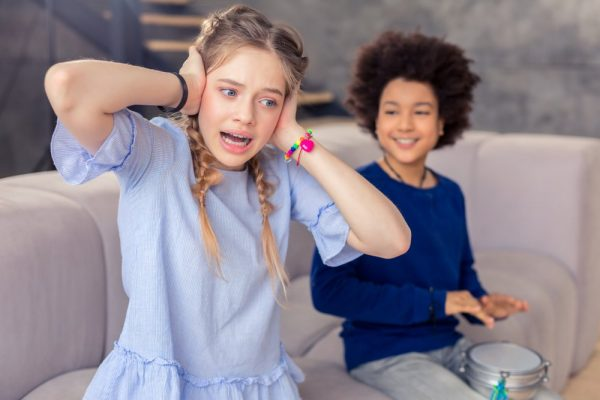 Sensory Overload | distraught girl covering ears while other child bangs on drum