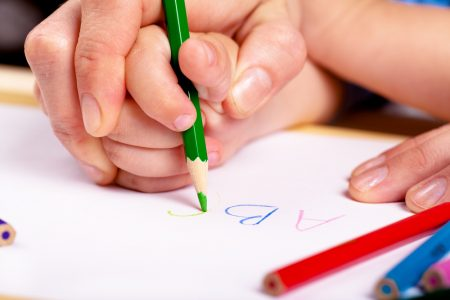 What Is Dysgraphia? | photo of adult hand guiding child's hand while writing letters