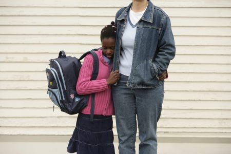 Anxiety Disorders In Childhood | photo of older child with backpack clinging to mother