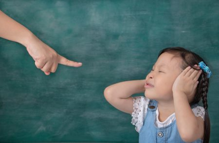 ODD in Children | photo of defiant child in front of chalkboard, with hands over ears, closed eyes and teacher's pointed finger.