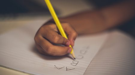 Dysgraphia Symptoms | photo close-up of child's hand practicing letter formation