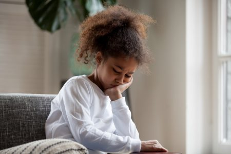 Anxiety In Kids | photo of sad anxious tween alone on couch