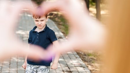 The Defiant Child | photo of sullen child framed by hands making shape of a heart