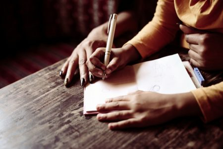 Dysgraphia Symptoms | photo of child sitting on mom's lap as she helps her write