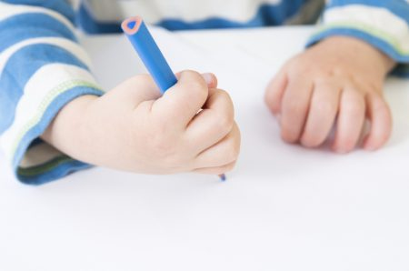 Dysgraphia Symptoms | photo of small child's hand awkwardly gripping colored pencil