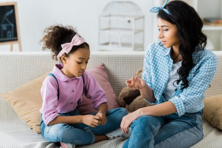 Social skills training | photo of mom and daughter having serious talk on sofa