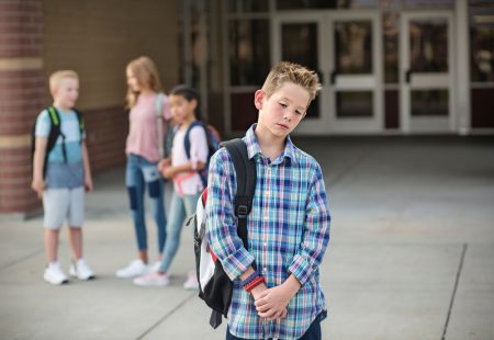 Social Skills For Kids | photo of tween boy excluded from group outside school