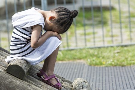 ADHD Social Skills | photo of isolated girl on playground with head in hands