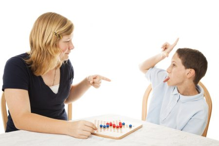 social skills training | photo of obnoxious winning child playing board game with family member