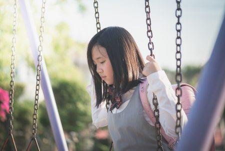 overcoming social anxiety | photo of sad school girl sitting alone on swings