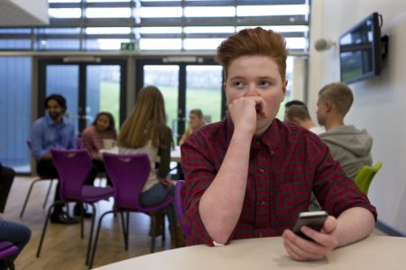 Social Anxiety In Children| photo of distressed teen alone in cafeteria